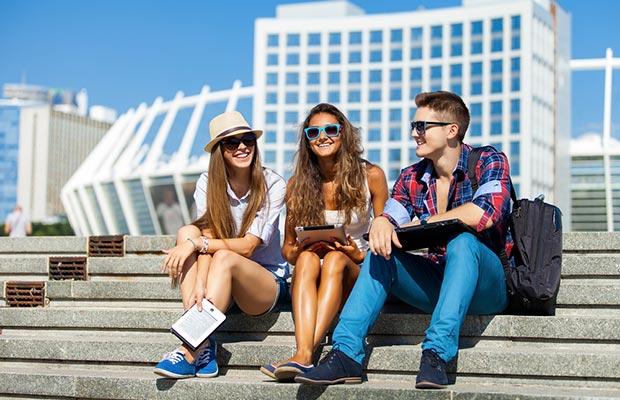 Curso verano. Tres jóvenes sentados en una escalera, con sol, actitud sonriente