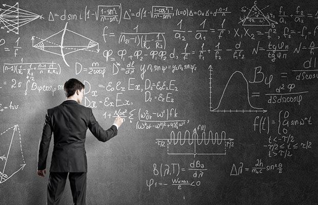 Grado en Física. Joven anotando en pizarra, llena, cálculos.