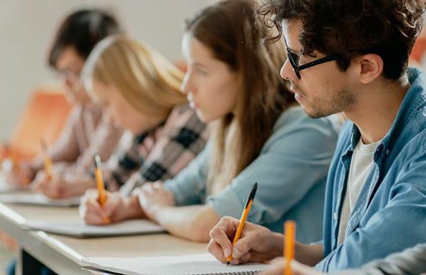 Portal exámenes. Estudiantes en aulario prestando atención y tomando notas.