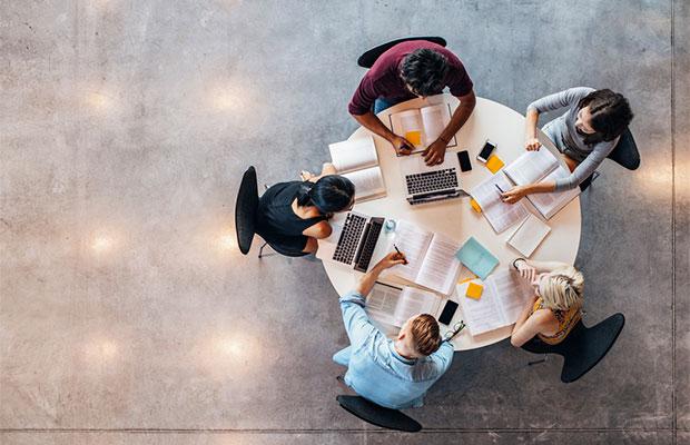 Extension Universitaria. Foto tomada desde arriba don se ven grupo de personas (4), trabajando en equipo.
