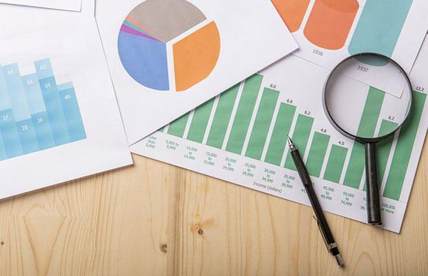 Portal transparencia. Hojas con representacion de datos en gráficos con bóli y lupa.