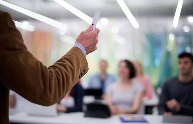 Profesores tutores. Brazo de un docente dirigiendose a los estudiantes impartiendo clase.