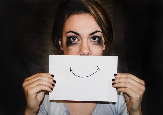 Teoría y Práctica de la Terapia Individual Psicodramática. Joven ojos amoratados, que se cubre la boca con una cartulina en la que está dibujada una sonrisa.