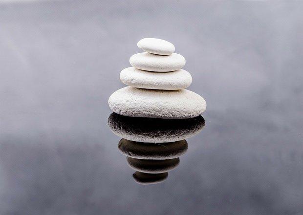 La función de lo simbólico en la Psicoterapia: La utilización de objetos intermediarios. Cuatro piedras blancas colocadas de mayor a menor sobre el reflejo de las mismas.