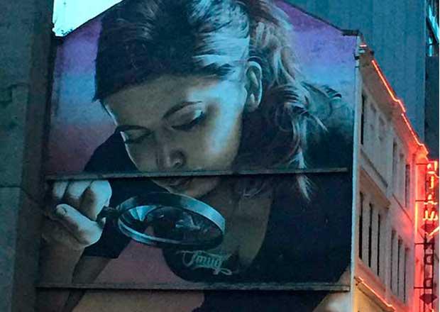 Curso de verano 2020 online. INSERCIÓN PROFESIONAL DEL CRIMINÓLOGO: BÚSQUEDA DE EMPLEO, RETOS Y OPORTUNIDADES. Graffiti lateral de edificio, mujer mirando a través de lupa.