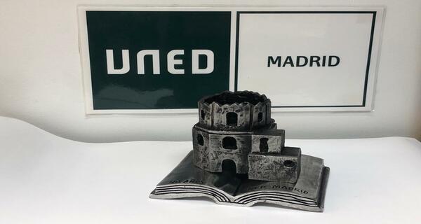 Escultura de la torre de la Antigua Iglesia de la Escuelas Pías, sobre un libro, fondo logo UNED MADRID
