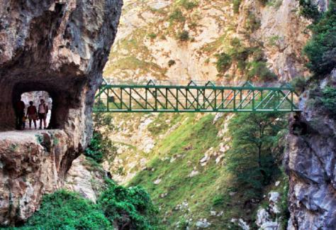 Puente entre montañas dos personas atravesando un pequeño tunel en la roca.