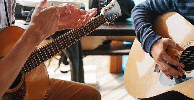 Dos personas con la guitarra clásica una de ellas dando explicaciones a la otra.