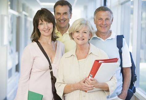 Gruo de cuatro personas senior sonrientes con carpetas y mochila.